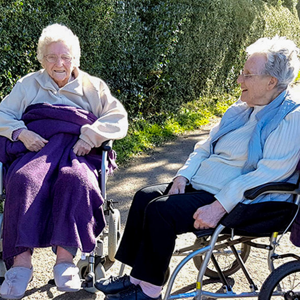 two residents together outside respite care